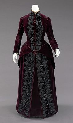 "Ensemble, Mme. Uoll Gross: ca. 1885, American, silk/synthetic/jet/feather.     ""This dress was designed to be worn in an open top carriage which, at the time, was a social event and everyone had to dress the part.    The bustle silhouette, although primarily associated with the second half of the 19th century, originated in earlier fashions as a simple bump at the back of the dress, such as with late 17th-early 18th century mantuas and late 18th- early 19th century Empire dresses. The full-blown bustle silhouette had its first Victorian appearance in the late 1860s, which started as fullness in skirts moving to the back of the dress. This fullness was drawn up in ties for walking that created a fashionable puff. This trendsetting puff expanded and was then built up with supports from a variety of different things such as horsehair, metal hoops and down. Styles of this period were often taken from historical inspiration and covered in various types of trim and lace. Accessories were petite and allowed for the focus on the large elaborate gowns. Around 1874, the style altered and the skirts began to hug the thighs in the front while the bustle at the back was reduced to a natural flow from the waist to the train. This period was marked by darker colors, asymmetrical drapery, oversize accessories and elongated forms created by full-length coats. Near the beginning of the 1880s the trends altered once again to include the bustle, this time it would reach its maximum potential with some skirts having the appearance of a full shelf at the back. The dense textiles preferred were covered in trimming, beadwork, puffs and bows to visually elevate them further. The feminine silhouette continued like this through 1889 before the skirts began to reduce and make way for the S-curve silhouette.""    Marking: Stamped on petersham: ""Mme Uoll Gross/136 East 19th St/N. Y."""