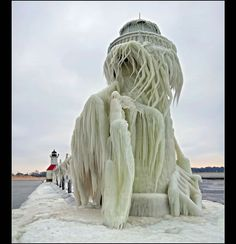 """Aftermath of the Winter Storm: The photographer described this photo as, """"30 foot tall outer light of the St. Joseph, Michigan after a severe winter storm. Waves on Lake Michigan were said to be over 20 feet high, which pounded the lighthouse and covered it in ice feet thick in places. Photo #6 by Tom Gill (A very brave photographer! ~A)"""