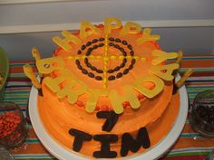 Nerf party cake with chocolate covered pretzel bullets, reeces pieces target and chocolate letters.