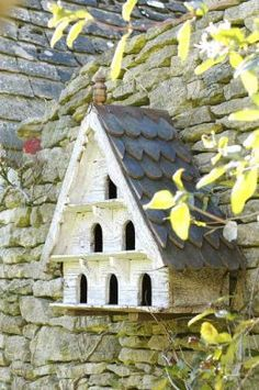 Hungarian, distressed white, wooden, three-tiered dovecote with wooden tiled roof and finial.