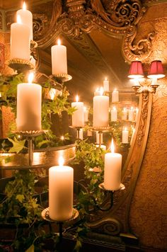 A four tiered stand wrapped in ivy features pillar candles.