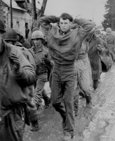 """Caption: """"A lanky GI, with hands clasped behind his head, leads a file of American prisoners marching along a road somewhere on the western front. Germans captured these American soldiers during the surprise enemy drive into Allied positions."""" Captured German photograph, December 1944"""