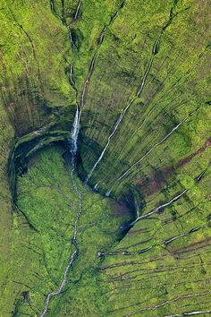"""Kauai's Mount Waialeale; generally considered the rainiest spot on Earth, drops water down 3,000-foot walls so sheer the sun simultaneously shines on all [its] walls only twice a year. Photo by Leona Boyd."""