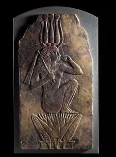Plaque in purplish-brown re-fired faience with representation in low relief of Yeweput as an infant king wearing the triple atef crown and emerging from a lotus flower: Ancient Egyptian, 23rd Dynasty