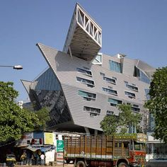 Pointed cantilevers project above an office block that is sandwiched between a corporate complex and a slum in Mumbai
