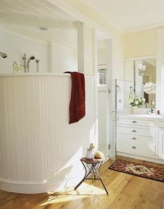Curved shower wall in bead board has beachy outdoor feel