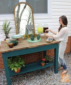 Blogger Lindsay Jackman pours a drink at her outdoor buffet made from an old factory cart. See more of her cute, boho backyard decor on The Home Depot Blog.