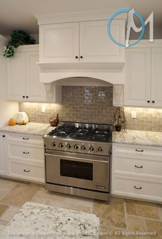 Colonial Gold with white cabinets presents a very clean look, accompanied by the grey tile backsplash and brushed metal range.