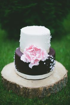 white and brown wedding cake with pink flower
