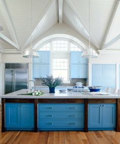 Bright kitchen cabinets in two tones of blue serve as the go-between for a generous kitchen island and soaring cathedral ceilings. | Photo: John M. Hal | thisoldhouse.com