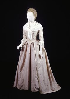 Silk open-skirt dress with matching peticot. The dress has a robe and matching underskirt. It is a pale mauve-pink silk of English manufactrure woven with a very small spot and with small flral sprays in various colours. The bodice's front edges meet and its centre back is lightly boned. The skirt front edges are bound with white silk ribbon. The tapes and loops make a 'polonaise' style skirt.     Date  1778 AD - 1785 AD