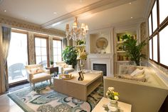 Intimate formal living room in light color scheme.  Design is ornate with off-white furniture, white custom fireplace and chandelier