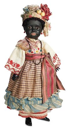 """Outstanding German Black-Complexioned Bisque Character,1358,by Simon and Halbig    22"""" (56 cm.) Bisque socket head with ebony-black complexion,brown glass sleep eyes,mohair lashes,black sculpted brows with highlight glaze,painted black lashes,accented nostrils,open mouth,shaded-coral very full lips,four porcelain teeth,pierced ears,black fleecy wig,black composition and wooden ball-jointed body,wearing very fine antique multi-layered costume."""