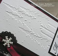 "In and Out Embossing - embossed the cardstock twice using two different embossing folders.  The orientation of the two embossed designs is reversed.  The ""Snowflakes"" pattern shows the ""positive"" or ""out"" embossing and the ""Tall Pines"" pattern shows the ""negative"" or ""in"" embossing."