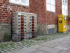 German street artist EVOL transforms banal urban surfaces into miniature lifelike buildings