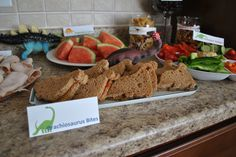 Dino themed food: Brachiosaurus Bites - sandwiches Stegosaurus Spikes - watermelon triangles  Herbivore Delight - veggie tray with hummus Velociraptor Claws - bugles Dinosaur Eggs - grapes Dinosaur Bones - pretzel sticks Tyrannosaurus Rex Tray - meat and cheese tray Dinosaur Track Cookies - sugar cookies with dino prints (use a dino toy to stamp them) and sprinkle cinnamon on top as dirt veggie tray, dinosaur parti, cheese trays, chees tray, dinosaur track, dinosaur bone, veggi tray, dinosaur egg