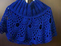 Mini poncho confeccionado em lã, de tricô e crochê.