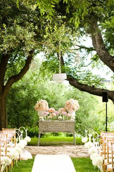 A vintage dresser, given a new coat of paint and covered with lots of floral arrangements, makes for a shabby chic ceremony backdrop. (Bonus tip - reuse the arrangements on your reception tables to save some cash!)