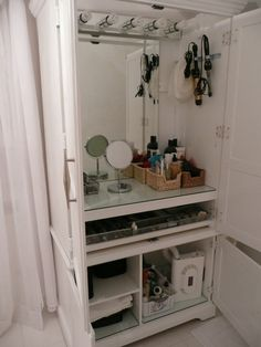 Armoire…converted to makeup station. A fresh coat of white paint, a refurbished vanity light and wire baskets bought at a Olies.