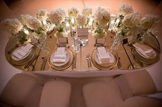 feathered back drop   sweetheart table covered in white roses   custom, mirrored stage   draped ballroom in sheer, white fabric   mirrored table tops, candles and soft lighting