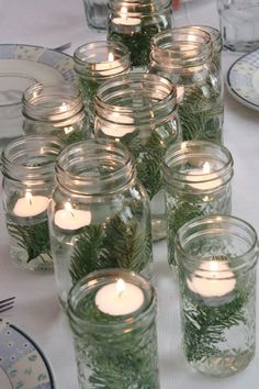 pine branches, water and candles in mason jars