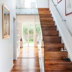 White hallway with walnut and glass staircase | Hallway decorating ideas