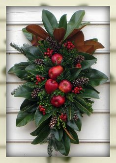 Love this swag with magnolia leaves, greens and apples along with a few skinny long pine cones!