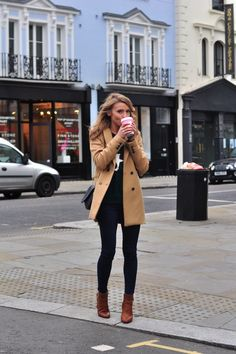 Brown double breasted coat, black shoes, dark jeans, and short boots.