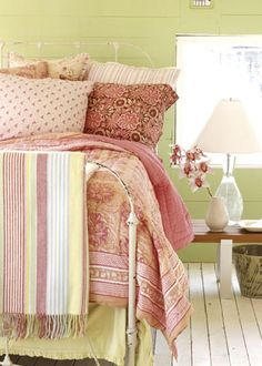 PRETTY BEDROOM DESIGN  Pump up the color quotient in your bedroom with a cheery paint color and pretty linens. The fresh green paint on the walls offsets the painted white floor. A combination of floral and striped bedding layers on the color. Fresh flowers are always a welcome addition in a bedroom.