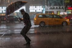 A commuter uses an umbrella while dodging high winds and heavy rain during a thunderstorm in midtown Manhattan, New York, July 18, 2012.