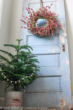 Stairwell decor- old door with red berry wreath and tree in a bucket