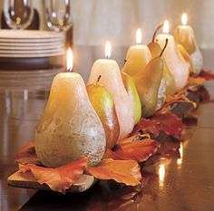 Layer a wooden tray, fake leaves, and fruit candles for a neat centerpiece.