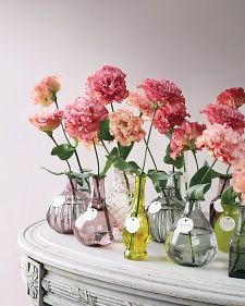 A single flower in a collection of bottles could be a pretty way to decorate your tables.