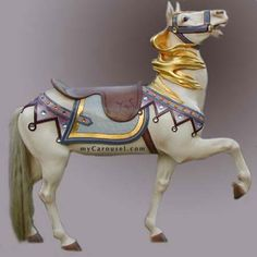 Charles Illions - New Price - $11,900  An elegant circa 1920 outside row stander strides out with upraised head and gold leaf blowby mane. The restored white horse carries bears fanciful trappings inset with many jewels and enhanced with gold leaf. Glass eyes and a natural horsehair tail. 57 long x 60 high..