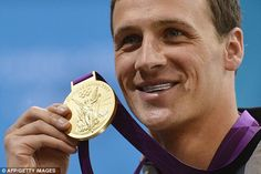 Bling: Lochte poses on the podium with his gold medal (and some patriotic dental wear) after the race
