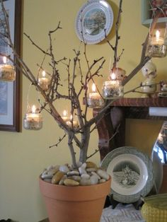 DIY deco... tree branch centerpiece held in pot by decorative rocks & adorned with baby food jars filled with bird seed, battery-operated tea lights