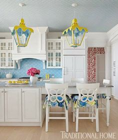 Shimmery water-blue backsplash, a wallpapered ceiling, whimsical lanterns, and bar stools covered in Lilly Pulitzer fabric... dream kitchen!