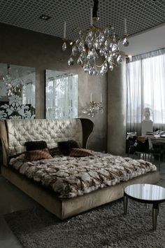 venetian plaster walls look like stone, mirrors with etched scroll patterns, crystal chandelier and wall sconces, exquisite padded headboard with curved sides, fur bedspread