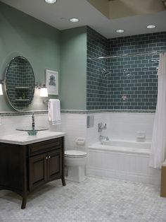 bathroom with subway tub surround and glass vessel sinkTile from the Tileshop, green gray walls, Kohler glass vessel sink, round pivot mirror, sconces, white carrara marble hexagon tiles floor and green ceramic subway tiles shower surround.