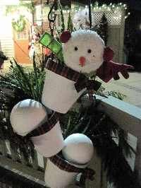 Snowman made  in painted clay pots, using a long hanging tipsy pole. Plaid ribbon and greens were added for color.