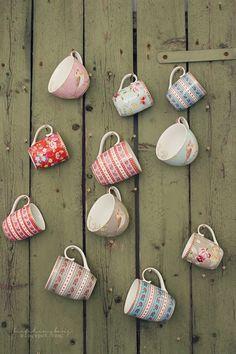 Random teacups hung against a wooden door