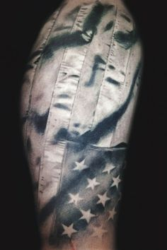 The fabric on this American flag tattoo by Megan Hoogland is so realistic! #InkedMagazine #flag #America #American #tattoo #tattoos #inked #realistic