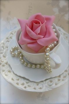 Pearls in a tea cup with a silk rose.