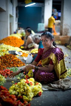 A woman creates flower garlands at the City Market in Bangalore (India).