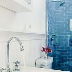 In the bathroom, blue tile and colorful accessories pop against an all white interior.