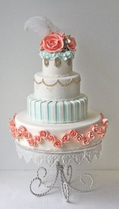 Blue, coral, white and gold vintage wedding cake with roses.