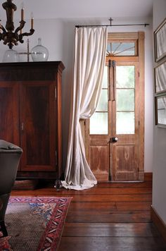 "Beautiful French Cypress Doors with early 1800's door hardware are adorned with  a woven old linen sheath from France.  early Louisiana 1820s beehive armoire. The floors are 2"" x 12"" ceiling joist from a school house demolition in the nearby town of Donaldsonville, Louisiana. A. Hays Town"