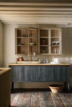 modern rustic kitchen in raw wood stained dark blue and and natural with wall units with woven basketware backs and glass doors by Devol and Sebastian Cox