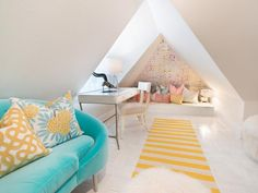 Sloped walls were kept white to keep this attic room from feeling too closed-in. Bright punches of color in the striped runner, accent wallpaper and sofa help highlight the unusual architecture without overwhelming the space. Design: Kriste Michelini/Photo: Jason Kisner