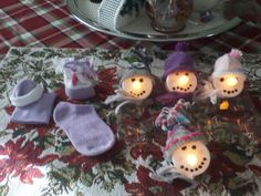My annual Christmas ornaments this year: Battery tea lights as base. Infant socks for hats. I got two hats out of every sock. Roll socks or cut fringe on top and tie. Spot glue hats on base of tea light. Add fishing line through the hat and Voila!!! I also added cut socks as scarves.  Used puffy paint for coal eyes and mouth. Merry Christmas.
